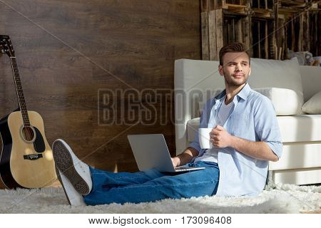 Handsome young man with laptop and cup sitting on carpet and looking away