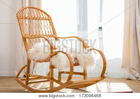rocking chair with woolly rug in bright room with sunlight