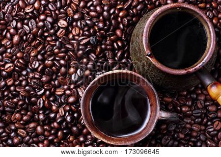 Turk and steaming hot coffee in clay cup on coffee beans.Turksih coffee.top view
