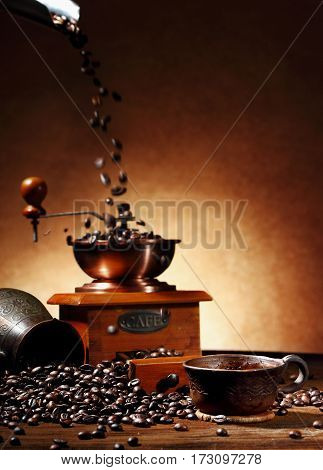 still life with coffee beans and clay cup and turk on. Cofffee beams pouring into old coffee mill motion effect and turk on the wooden background.Selective focus