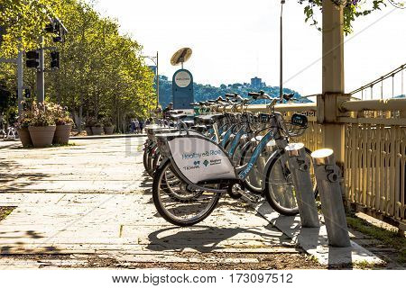 Pittsburgh Pennsylvania USA - July 31 2016: A row of Healthy Ride rental bicycles lined up on the street as tourists walk in the background.