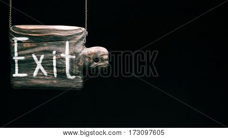 Old-fashioned hanging wood sign of cutting board with text 'Exit'. Isolated over black background