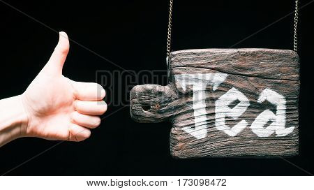 Old-fashioned hanging wood sign of cutting board with text 'Tea'. Hand gesturing thumb up. Isolated over black background