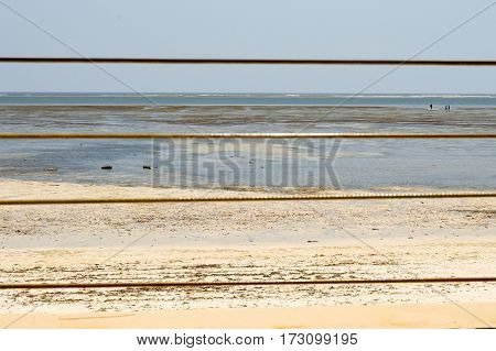 Yellow steel cable with the ocean in background on the beach of Bamburi in Kenya