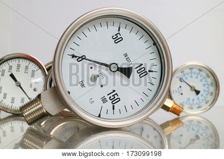 Row of metal steel high pressure gauge meters or manometers with brass fittings on tubing pipeline at LNG or LPG natural gas distribution station plant or factory facility isolated on white background.Pressure gauge in oil and gas production process for m