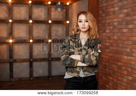 Young Beautiful Stylish Woman In Military Jacket On A Background Of Lights