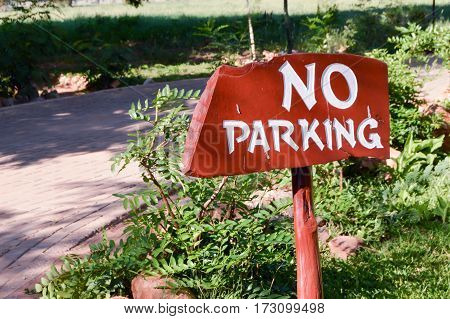 Non-parking sign in white letters on a wooden background at the entrance of a hotel