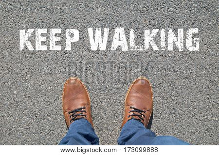 Feet on the street with text KEEP WALKING