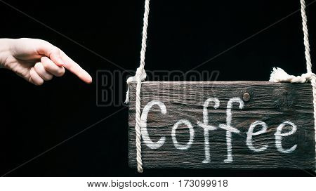 Old-fashioned hanging wood sign with text 'Coffee'. Finger pointing to the sign. Isolated over black background