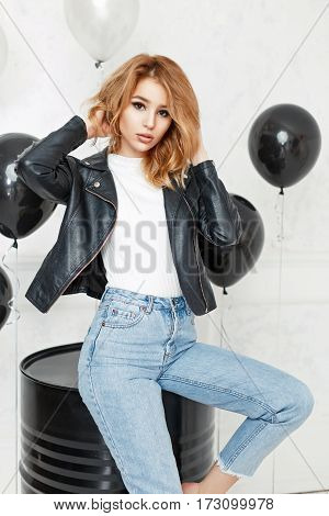 Beautiful Young Blonde Girl In A Black Leather Jacket And Blue Jeans Posing In Studio On Light Backg