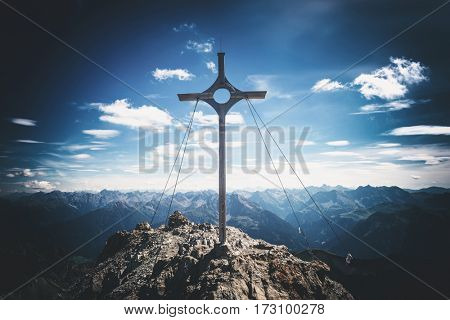 Summit marker on Grosser Krottenkopf, the highest peak in the Austrian Prealps, overlooking a vista of distant mountain ranges and a sign of sporting achievement