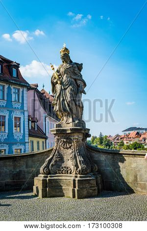 Low angle view of bronze statue of Kunigunde with gold crown and scepter on a pedestal
