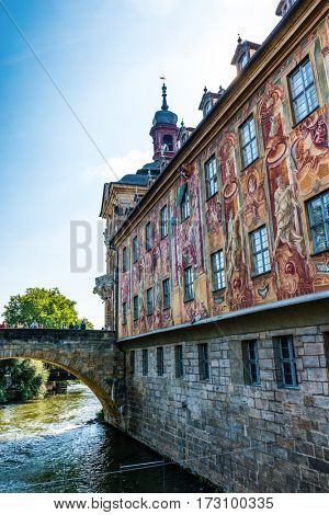 Mural covers wall of medieval German Bamberg Town Hall building with attached stone bridge