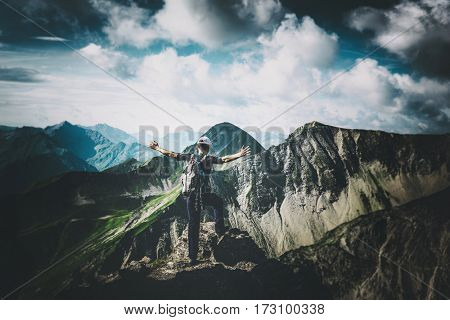 Climber celebrating his achievement on a high rocky alpine summit standing with outstretched arms overlooking a vista of high alps and mountain ranges with steep valleys