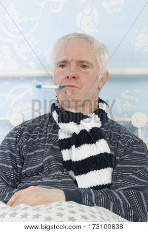 Sick man with thermometer in mouth