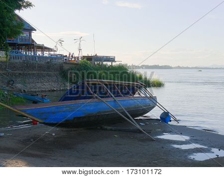 Boat in drydock on the side of a river