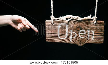 Vintage hanging wood sign with text 'Open'. Finger pointing to the sign. Isolated over black background