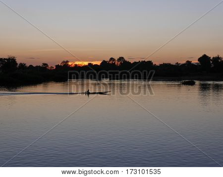 An asian long tail boat on river mekong in evening sunset light