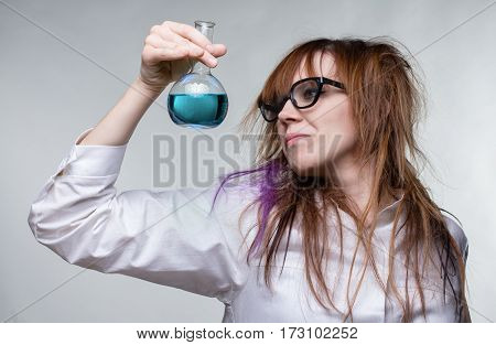Scientist shaggy woman with blue liquid on gray background