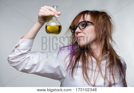 Scientist shaggy woman with yellow liquid on gray background