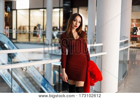 Beautiful Young Woman In A Red Dress With A Coat Walks In The Store