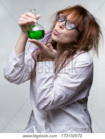 Shaggy woman with green liquid on gray background