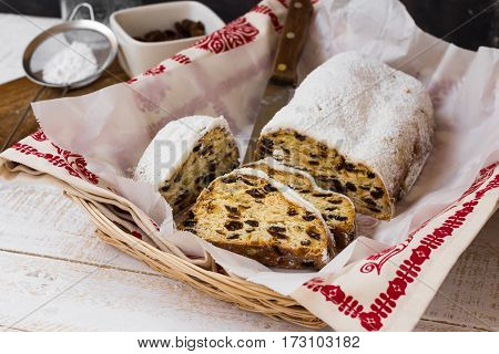Christmas stollen cut into slices in wicker basket with ornamented towel ingredients sieve with caster sugar on wood kitchen table rustic kinfolk style