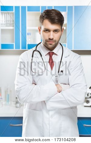 portrait of serious doctor in medical uniform in lab