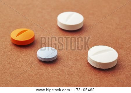 Pills over a brown background. Medicament treatment. Health care photo
