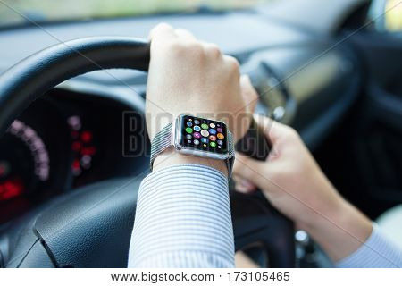 Man hands and smart touch watch with home screen icons apps driving car