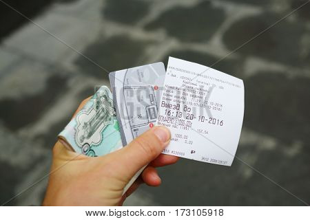 MOSCOW - OCT 20, 2016: Male hand holds ticket for parking in Empire Tower in Moscow City, moneys and plastic card