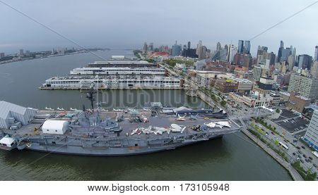 NEW-YORK - SEP 07, 2014: Cityscape and ship USS Intrepid (CV-11) with Sea-Air-Space museum near shore. Aerial view. Museum exhibits include 28 authentically restored aircraft.