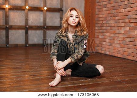 Trendy Stylish Woman In Military Jacket And Black Jeans Sitting On A Wooden Floor