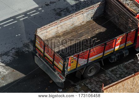 Truck with an empty and dirty bodywork parked in the street