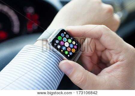 Man hands and smart touch watch with home screen icons apps in car
