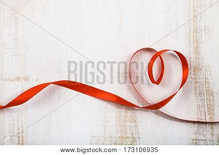 Red Ribbon In Heart Shape On A Wooden Background.