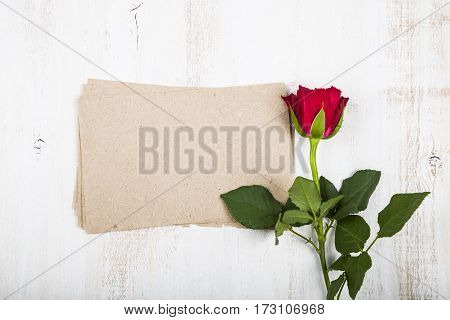 Red Rose And Paper For Congratulations On A Wooden Background.