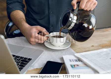 Partial view of man pouring coffee in cup on desk with laptop and smartphone