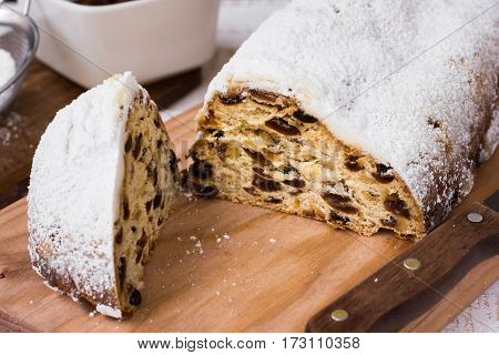 Homemade Christmas stollen cut off piece on wood board with knife ingredients in background top view close up