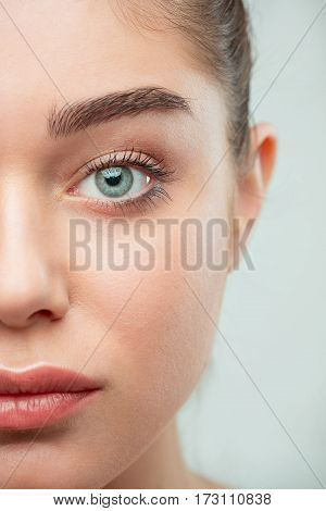 The beautiful female half face. The perfect and clean skin of face on gray