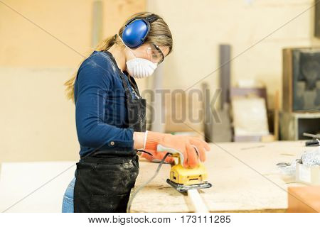Woman Sanding Some Wood In A Workshop