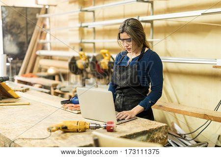 Female Carpenter Using A Laptop