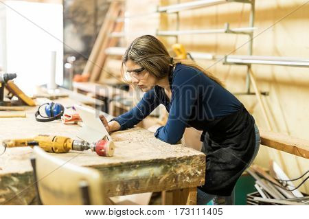 Profile viewo of a young woman looking at a tablet computer while working in a woodshop poster