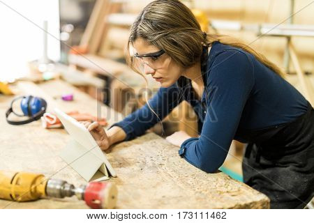 Woman Using Tablet In A Woodshop
