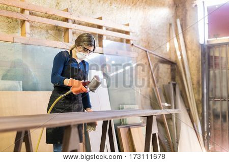 Woman Painting Table In A Woodshop