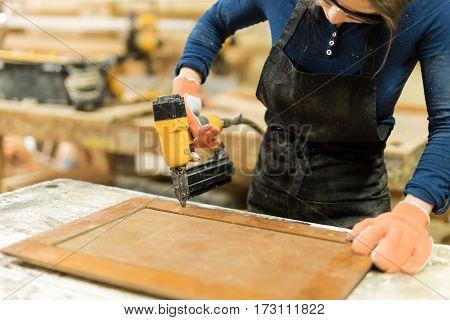 Woman Using Nail Gun On Some Wood