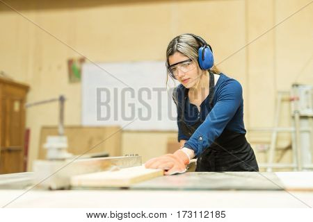 Pretty Female Carpenter Using A Table Saw