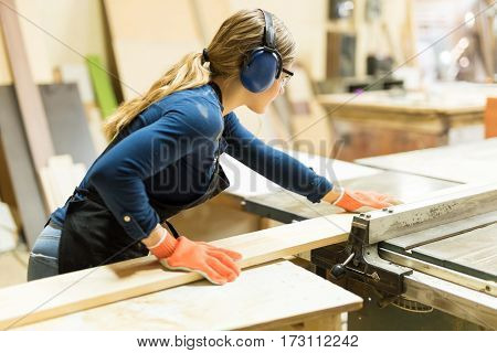 Woman Cutting Some Wood With A Table Saw