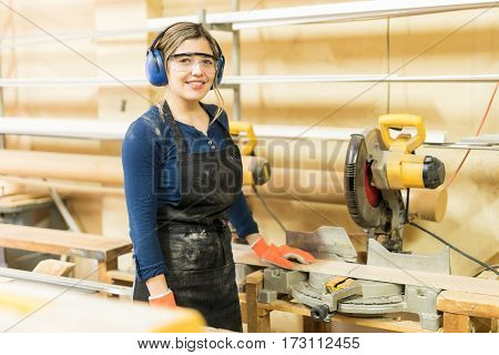 Pretty Female Carpenter Using Power Tools