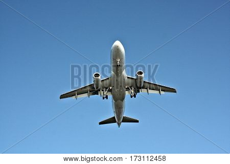 Airliner from underneath with it's silver body highlighted against a vivid blue sky